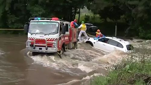 NSW SES and Fire and Rescue crews were called in to tether the car so it would not float further down the rising floodwaters near Taree NSW (Supplied).