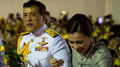 The royal couple greet royalist supporters outside the Grand Palace in Bangkok on November 1.