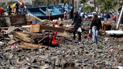 People walk through the debris. (AAP)