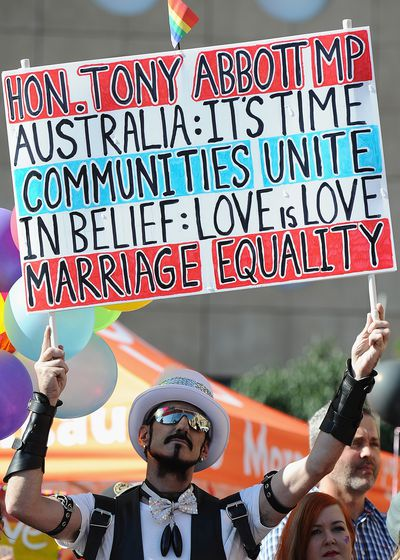 Marriage equality activists hold signs during a Same-Sex Marriage march at Queen Gardens in Brisbane. (AAP)