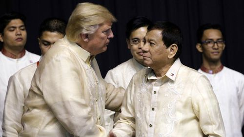 President Donald Trump shakes hand with Philippines President Rodrigo Duterte during the gala dinner. (AAP)
