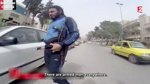 Men are seen carrying assault rifles throughout the city. (France 2)