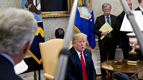 John Bolton listens to Donald Trump speaking in the Oval Office. (AAP)