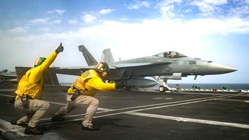 An F/A-18E Super Hornet from the 'Pukin' Dogs' of Strike Fighter Squadron 143 on the flight deck of the Nimitz-class aircraft carrier USS Abraham Lincoln.