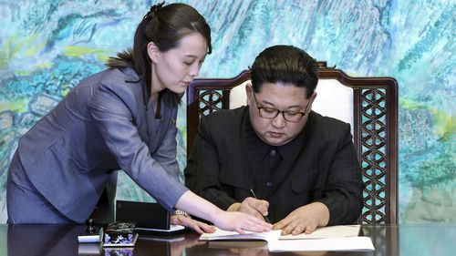 North Korean leader Kim Jong Un signs a joint declaration, with the help of his sister Kim Yo Jong (L), a senior official of the ruling Workers' Party, after talks with South Korean President Moon Jae In at the House of Peace in the border village of Panmunjeom on April 27, 2018.