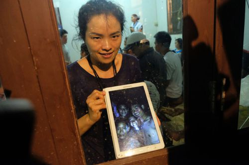 A parent of one of the rescued children shows off the selfie of the boys taken inside the cave. Picture: Getty