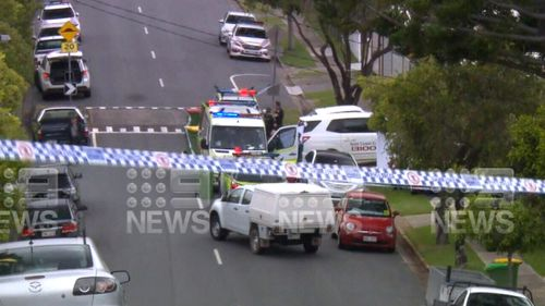 Police vehicles inside a cordoned off crime scene, where a Gold Coast man was found dead