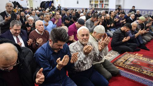 Muslim believers pray in a mosque for the victims of the shooting in Hanau, Germany, Friday, Feb. 21, 2020.