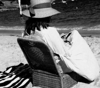 Nikki Gemmell sitting on a chair at the beach