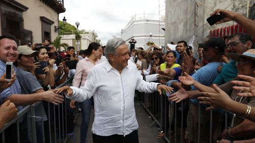 Mexico's President-elect Andres Manuel Lopez Obrador greets supporters in Mazatlan, Mexico, Sunday, Sept. 16, 2018. Lopez Obrador kicked off his nationwide tour with a new security group of 20 people who will rotate five at a time to accompany him everywhere, with the goal of allowing the incoming president to interact with voters.