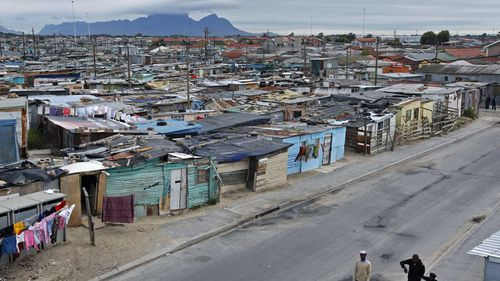 A township on the outskirts of Cape Town, South Africa, with Table Mountain in the background. (AAP)