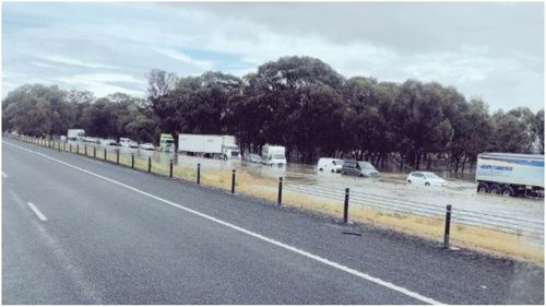Dozens of cars and trucks trapped in flood water on Victoria's Hume Freeway.