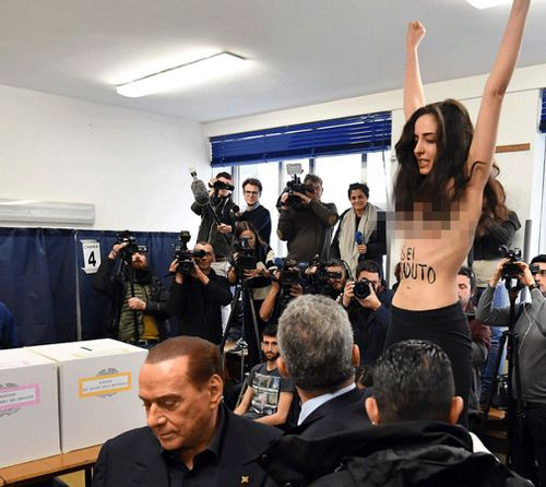 Silvio Berlusconi leaves after being confronted by a protester at an Italian election polling station on Sunday, March 4. (AAP)