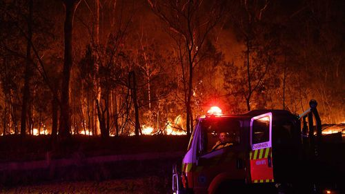 A RFS fire fighter with the Charmhaven unit monitors a small flare up on New Years Day on the Kings Highway near Batemans Bay.