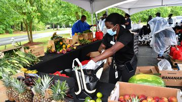 A volunteer prepares a food package during Goodr Pop-Up Grocery Store Shopping Experience at Lucky Shoals Park on May 08, 2020 in Norcross, Georgia.