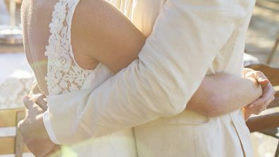 Bride and groom hugging in sunlight