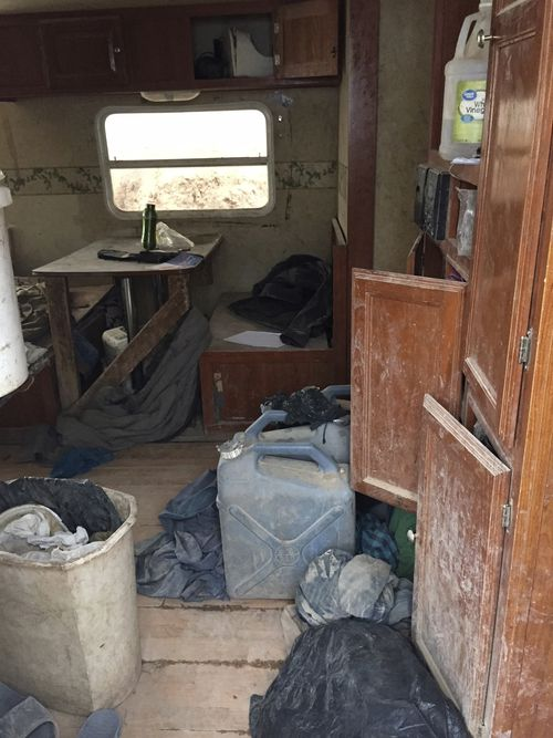 This Friday, Aug. 3, 2018, photo released by Taos County Sheriff's Office shows a rural compound after being found in filthy conditions during an unsuccessful search for a missing 3-year-old boy in Amalia, N.M. Law enforcement officers searching the compound for the missing child didn't locate him but found 11 other children in filthy conditions and hardly any food, a sheriff said Saturday. The children ranging in age from 1 to 15 were removed from the compound and turned over to state child-welfare workers, Taos County Sheriff Jerry Hogrefe said.in Taos, N.M. (Taos County Sheriff's Office via AP)