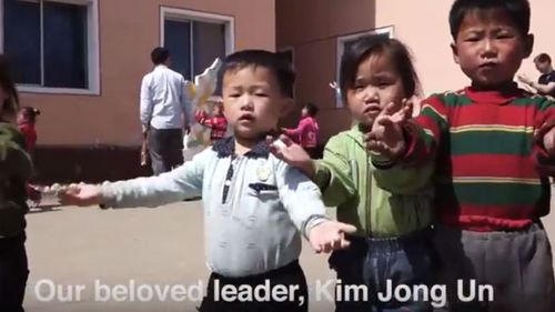 """A screen shot of children in North Korea dancing while singing about their """"beloved leader"""". (YouTube)"""