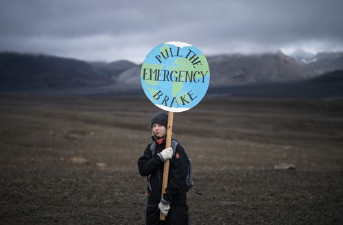 A girl holds a sign that reads 'pull the emergency brake' as she attends a ceremony in the area which once was the Okjokull glacier, in Iceland