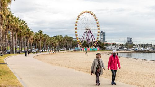 People are seen walking wearing face-masks along the Geelong Waterfront.