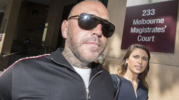 Former bikie boss shoves female photographer outside court