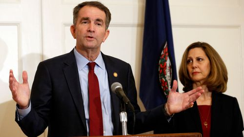 Virginia Governor Ralph Northam, left, with his wife Pam talks to the media in the governor mansion.