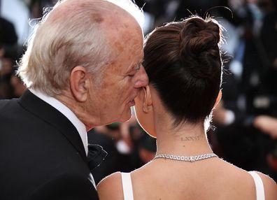 Bill Murray whispers into Selena Gomez's ear.