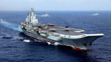 Two J-15 fighter jets of the PLA (People's Liberation Army) Navy prepare to take off from China's aircraft carrier, The Liaoning, followed by destroyers and frigates during a naval exercise in the western Pacific