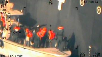 This image released by the US Department of Defence, taken from a US Navy helicopter, shows what the Navy says are members of the Islamic Revolutionary Guard Corps Navy removing an unexploded limpet mine from the M/T Kokuka Courageous.