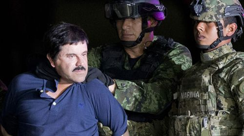 Soldiers march the notorious drug lord to a hangar ahead of transportation back to the prison he escaped from earlier this year. (AAP)