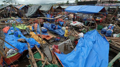 Filipino vendors collect items at a damaged market in Polangui. (AAP)