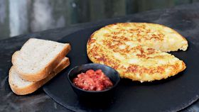 Tortilla de patatas with crushed tomato salad
