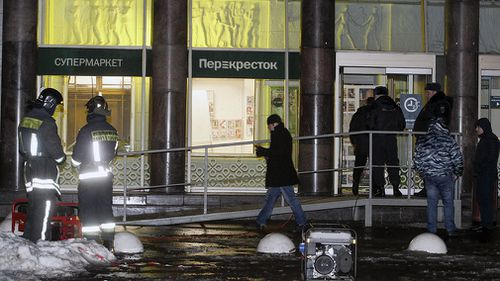 Police stand at the entrance of a supermarket, after an explosion in St.Petersburg, Russia. (AAP)