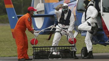 Officers of the National Search and Rescue Agency unload the body of an AirAsia victim. (AAP)
