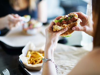 A woman eating a burger in a restaurant.