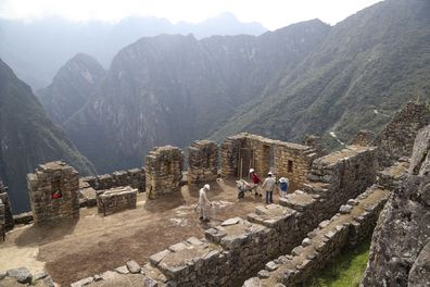 Maintenance workers clean Machu Picchu, which has closed during the Covid-19 pandemic.