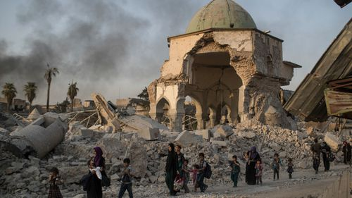 Fleeing Iraqi civilians walk past the heavily damaged al-Nuri mosque. (AAP)