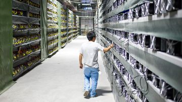 A technician walks by rows of super computers inside a Bitcoin mining facility in West Sichuan. The facility's 10,000 super computers solve mathematical equations around the clock to produce the virtual currency.