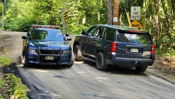 New York State Police block off a road near the scene where the body of Roy Den Hollander was found.
