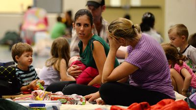 People take shelter ahead of the arrival of Cyclone Ita in an evacuation centre in Cooktown. (AAP)