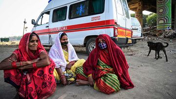 Women mourn for a relative at a mass crematorium site on the banks of the Ganges river in Allahabad, India.
