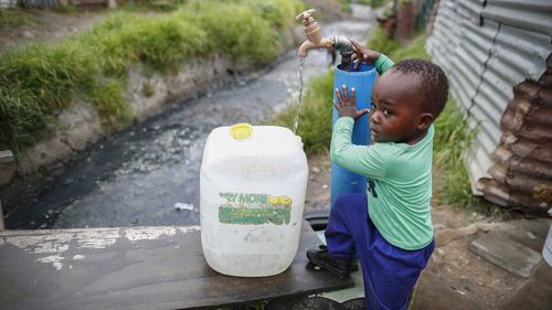 A little boy in Masiphumelele settlement in Cape Town fills out a container from a communal tap. (AAP)
