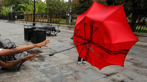 A man in the French Quarter plays with his umbrella in the wind of Tropical Storm Barry in New Orleans, Louisiana.