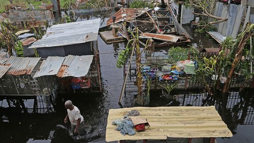 Farmer Victor Lozada searches for items that can be salvaged from his shed in Loiza. (AAP)