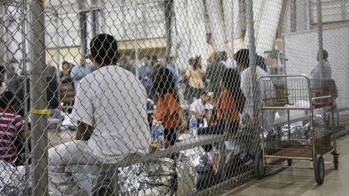In this photo provided by US Customs and Border Protection, people who've been taken into custody related to cases of illegal entry into the United States, sit in one of the cages at a facility in McAllen, Texas, Sunday, June 17, 2018.