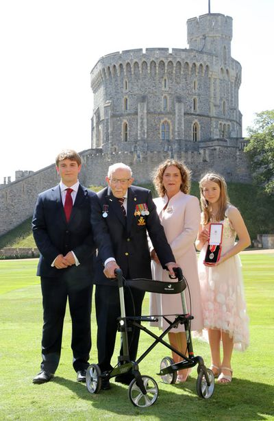 Captain Sir Thomas Moore poses with his family after being awarded with the insignia of Knight Bachelor by Queen Elizabeth II at Windsor Castle on July 17, 2020 in Windsor, England.