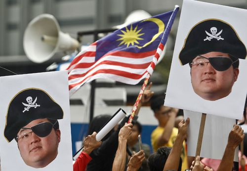 Protesters hold portraits of Jho Low illustrated as a pirate during a protest in Kuala Lumpur last month.