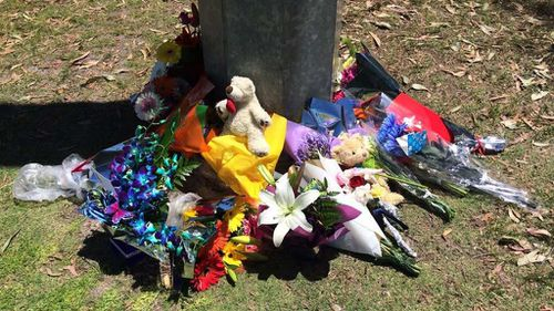 Flowers and teddy bears have been left at the lake where the body of toddler Sam Trott was found. (9NEWS)