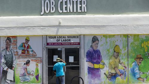A worker looks inside the closed doors of the Pasadena Community Job Center in Pasadena, Calif., Thursday, May 7, 2020, during the coronavirus outbreak.