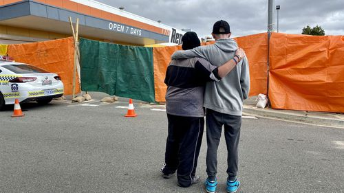 Two boys whose friend was killed when the three of them were sleeping rough in a skip bin embrace in Port Lincoln, South Australia.